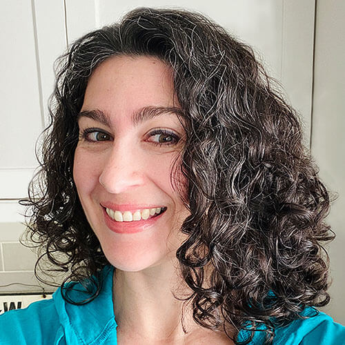 shot of a smiling woman. Her hair is curly with glossy, smooth, and well-defined curls.