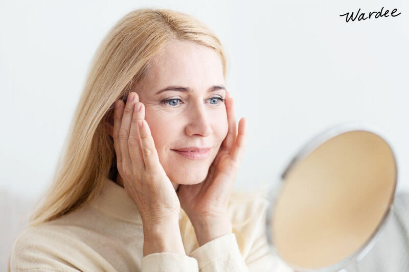 woman in her 50s or 60s touching her face while smiling and looking in a mirror