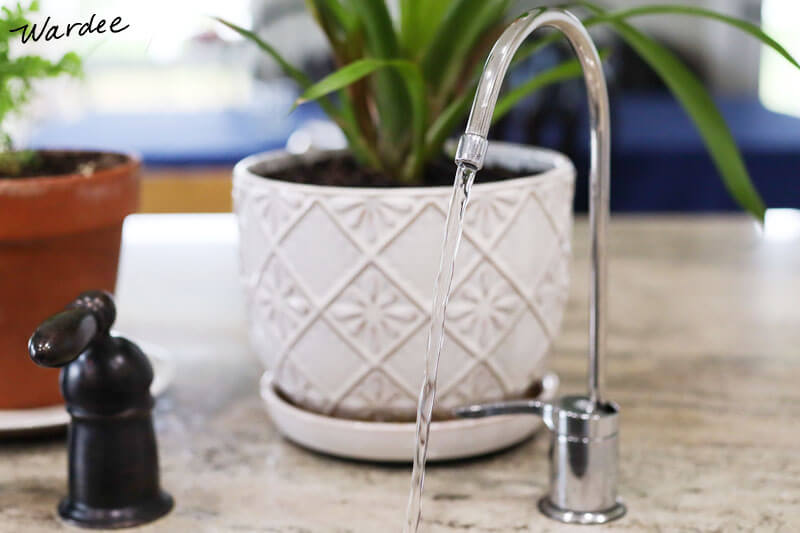 pure, filtered water coming out of a stainless steel faucet